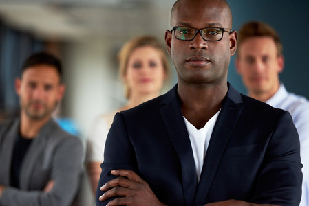 Black male executive with arms crossed facing camera