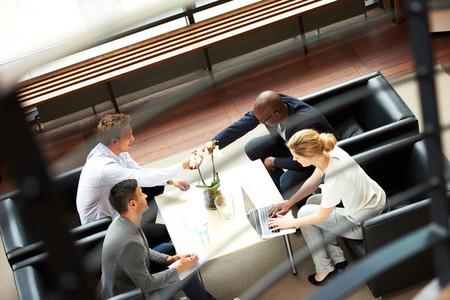 Black man and white man shaking hands during work meeting