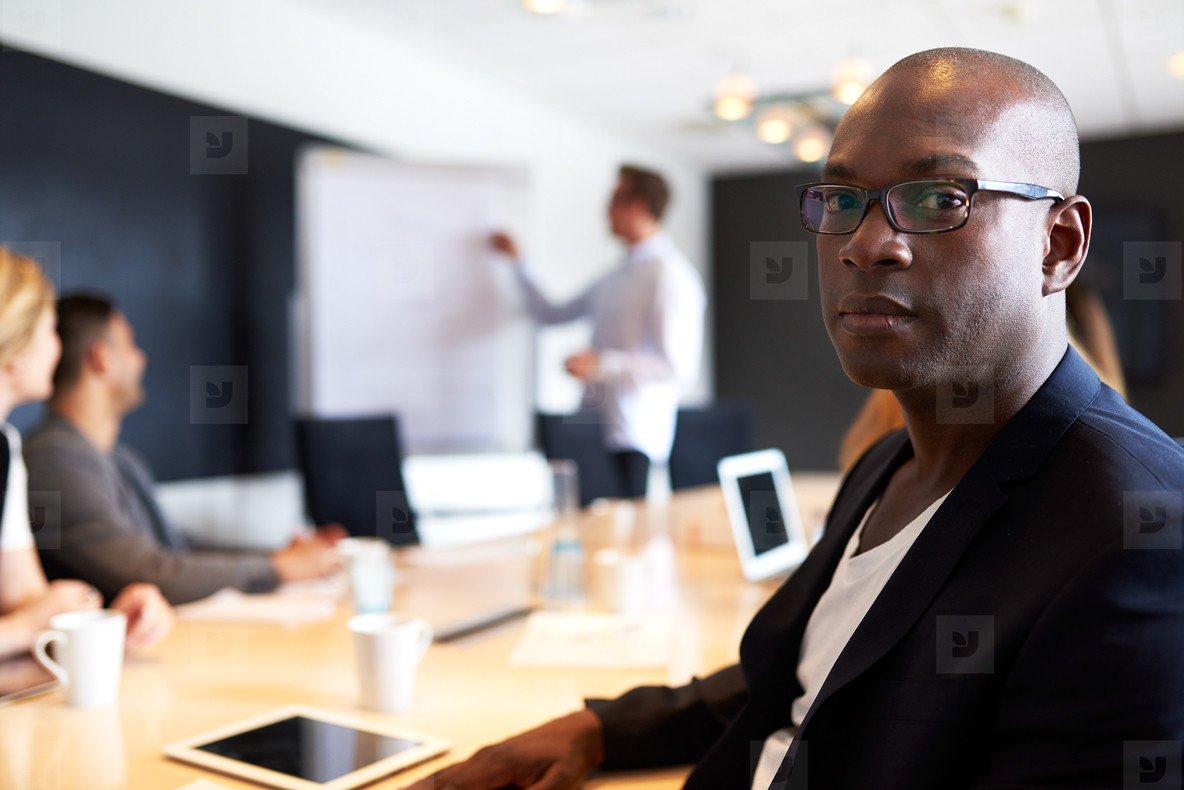 Black male executive facing camera with serious expression