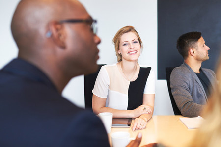 White female executive smiling at camera during meeting