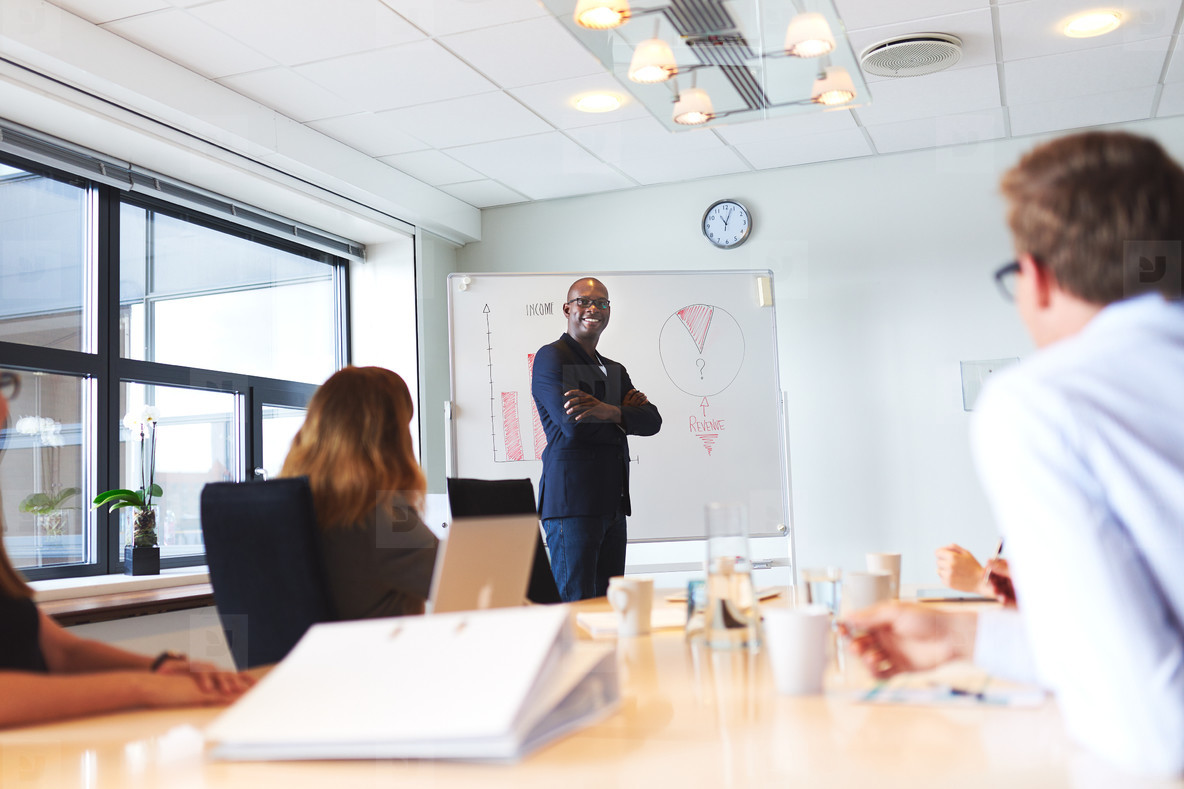 Black male executive standing next to whiteboard smiling