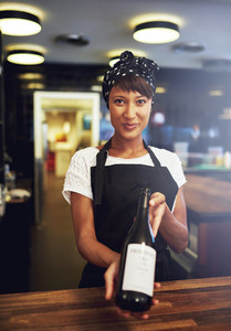 Smiling young waitress presenting a bottle of wine