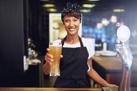 Smiling friendly waitress serving a beer