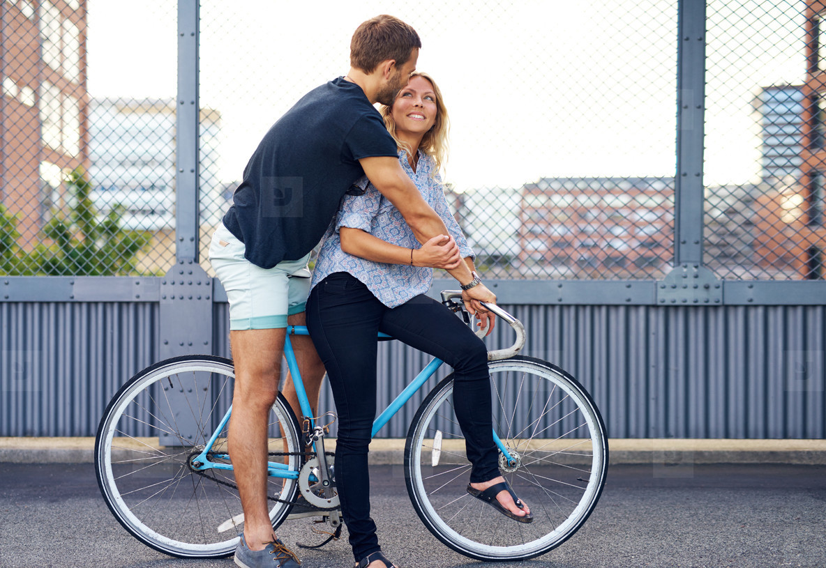 Sweet Young Couple on a Bicycle at the Street