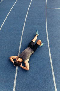 Sprinter relaxing by lying on the running track