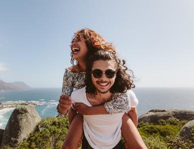 Man giving piggyback ride to his girlfriend