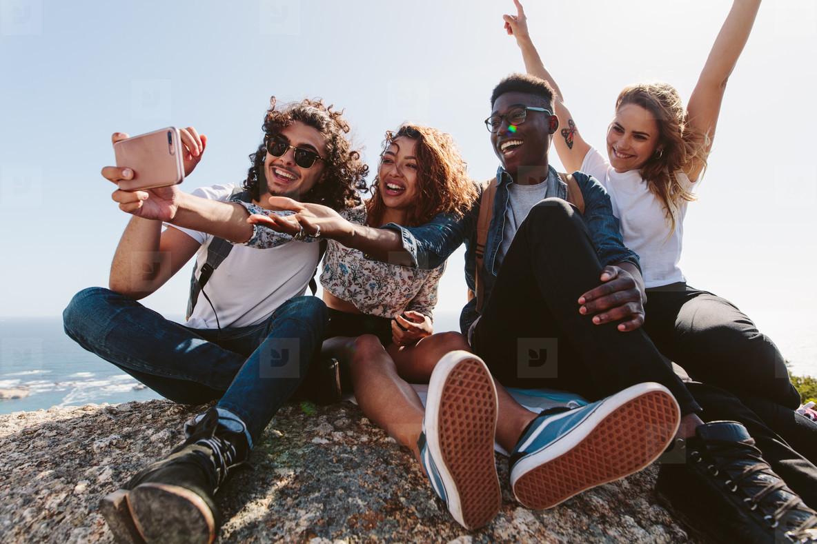 Friends sitting on top of a mountain taking selfie