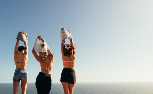 Women removing their tops against seascape
