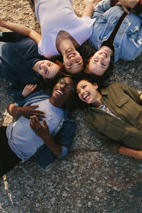 Diverse friends lying on ground in circle outdoors