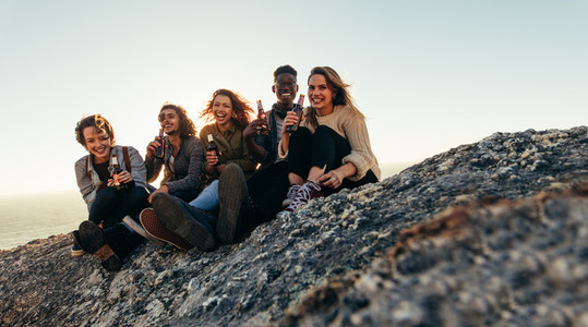 Diverse group of friends having beers on mountain top