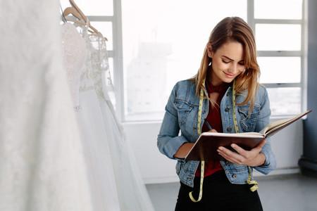 Dressmaker designing bridal wear pattern on diary