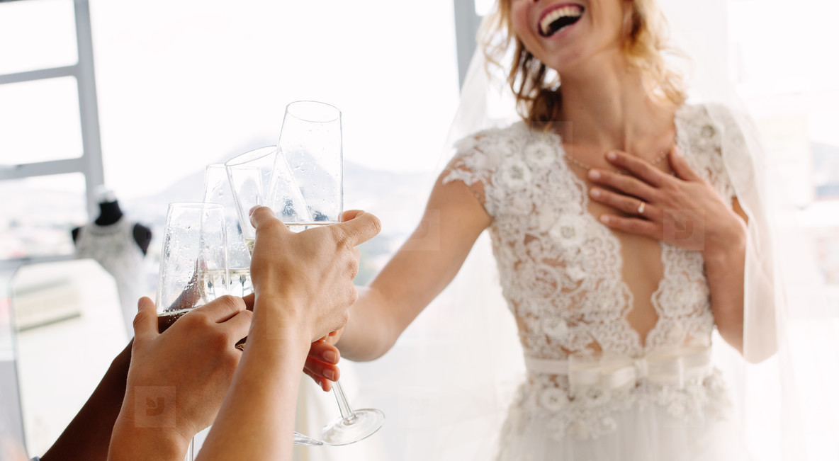 Bride with friends drinking champagne in bridal boutique