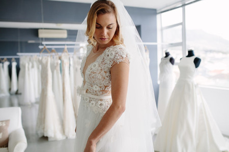 Beautiful woman trying on bridal gown in boutique