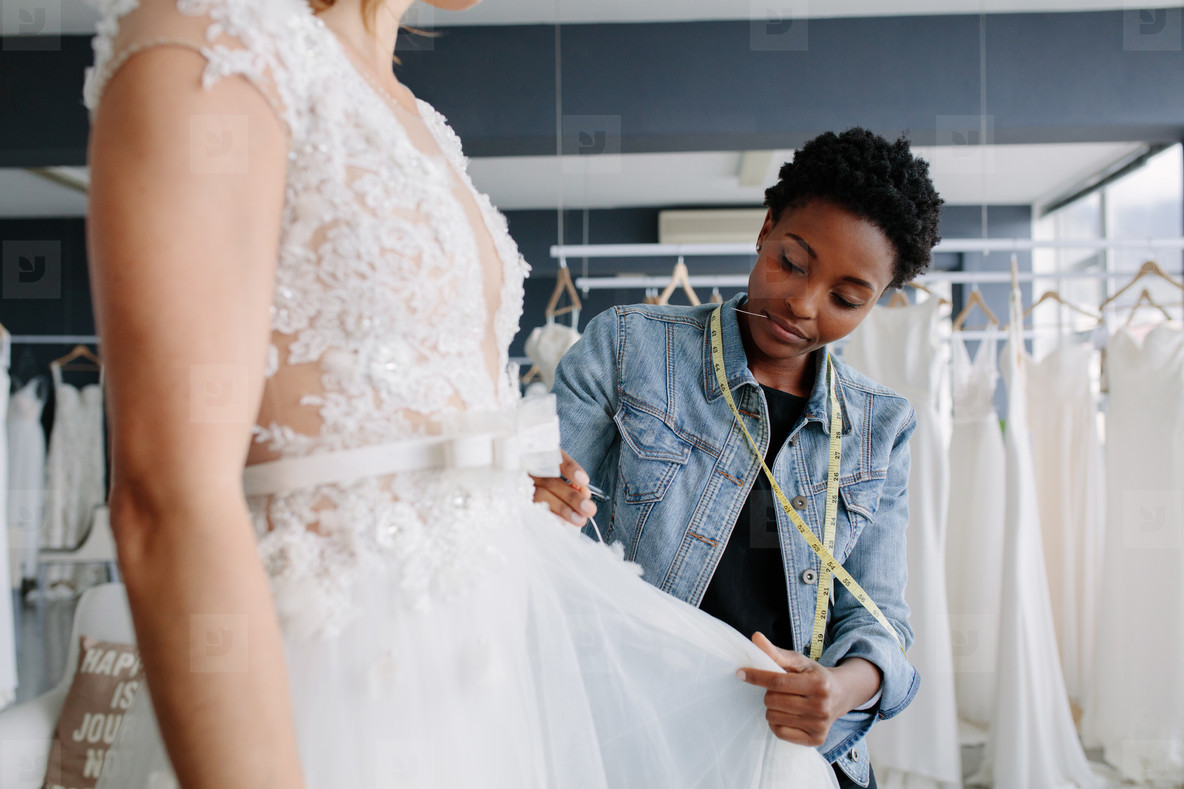 Professional wedding dress designer fitting bridal gown to woman