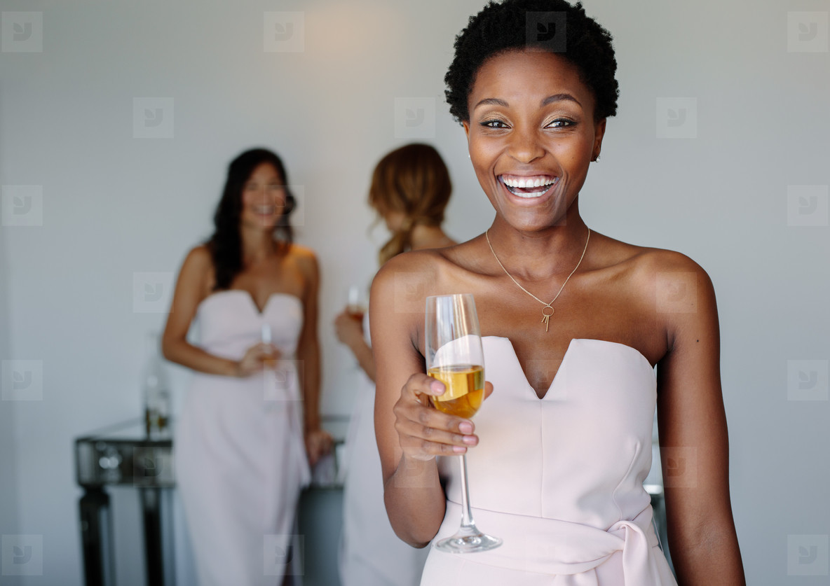 Beautiful bridesmaid having wine on wedding day
