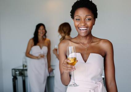 Beautiful bridesmaid having wine on wedding day