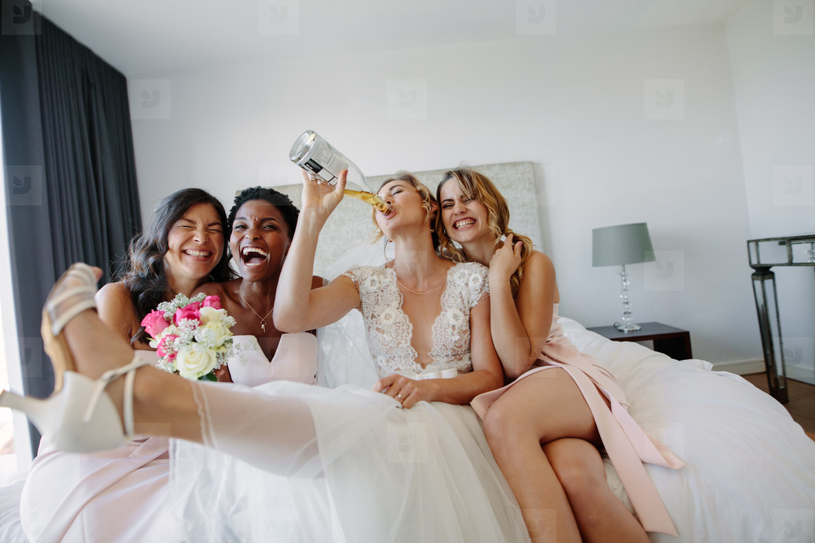 Bride and bridesmaids having fun before wedding