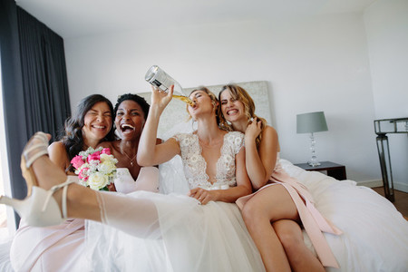 Bride and bridesmaids having fun before wedding