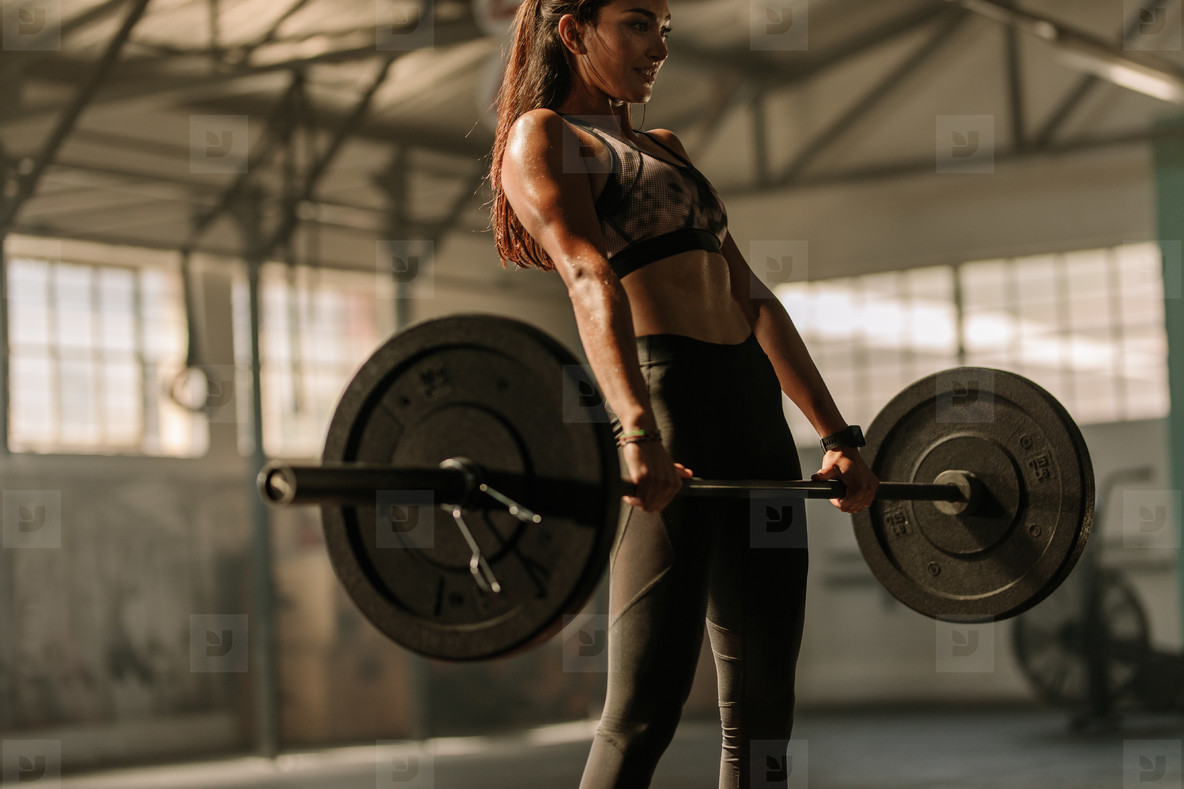 Determined and strong woman with heavy weights