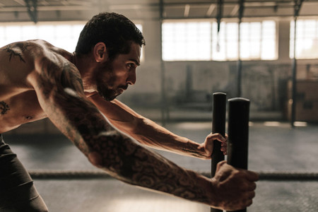 Man performing powerful exercise at cross training gym
