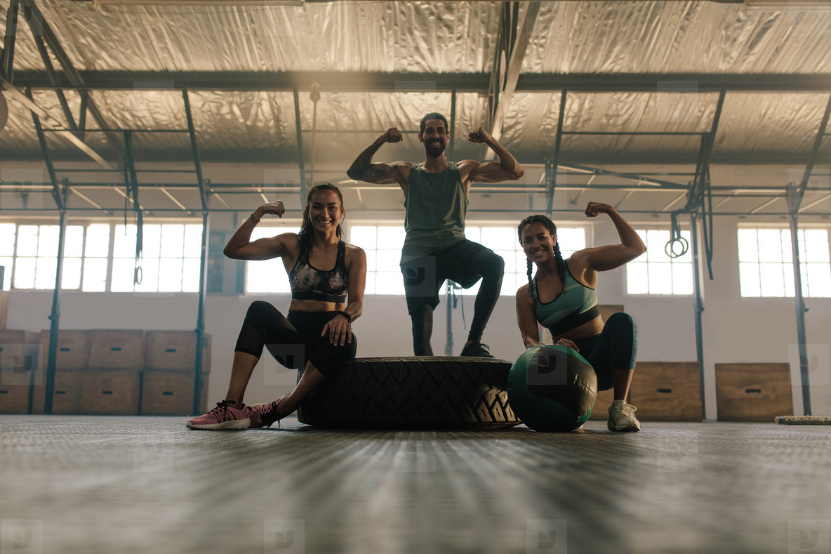 Young people posing and flexing their muscles in gym