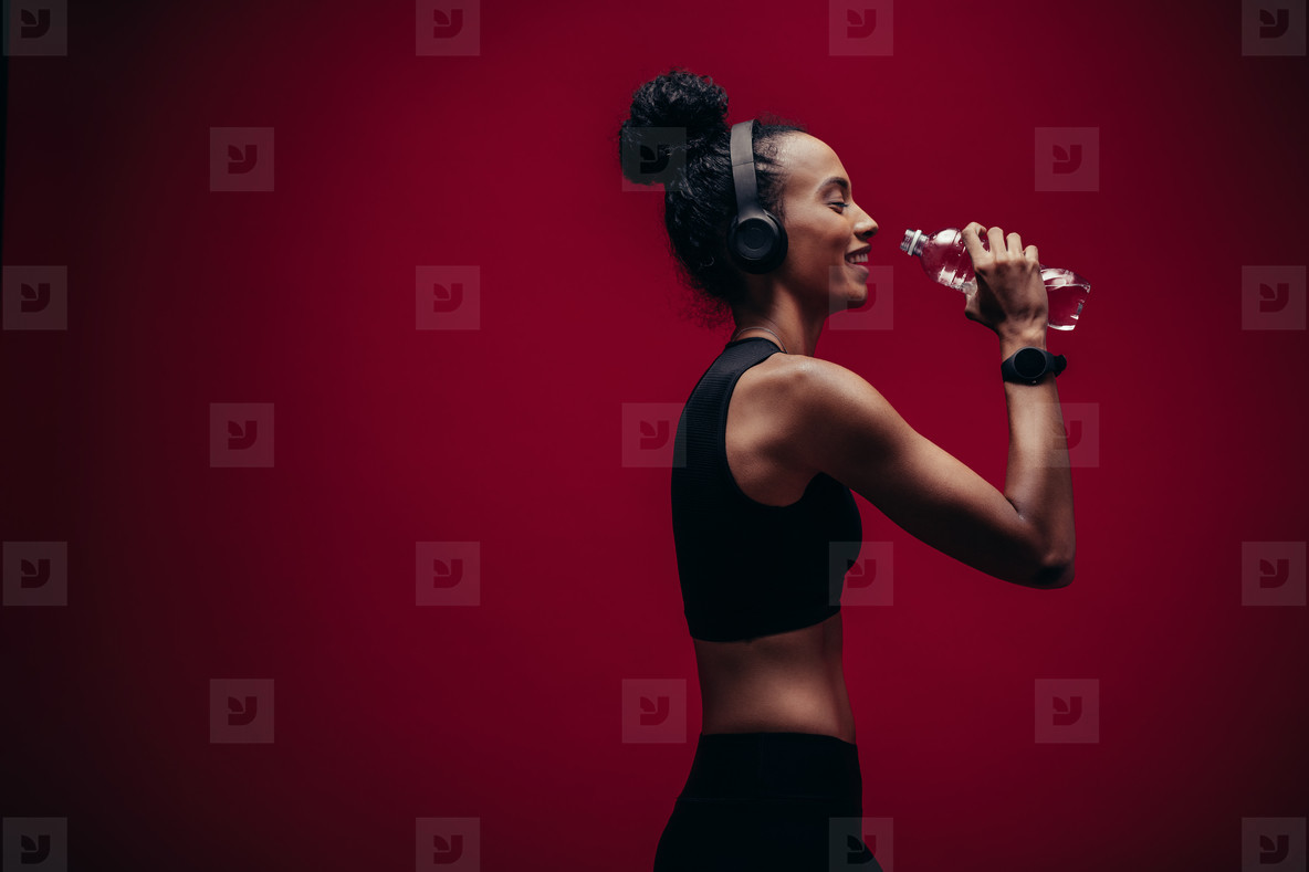 Fitness woman drinking water after workout