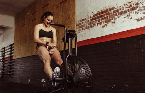 Woman doing cardio exercise on bike at gym