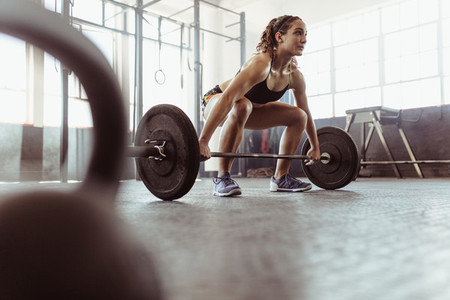 Woman lifting a barbell at the gym