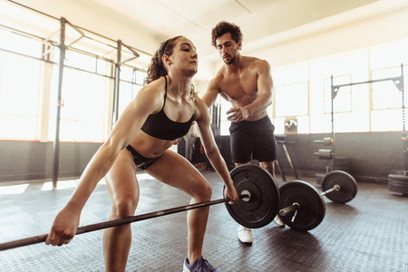 Personal trainer with woman lifting barbell