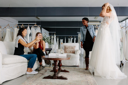 Woman trying on wedding dress in a shop with friends