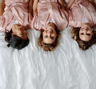 Three young women lying on bed and smiling