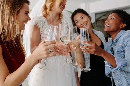 Woman in bridal gown toasting champagne glasses with friends