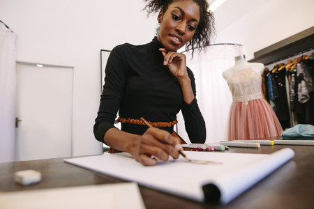Fashion designer working on her designs at her desk