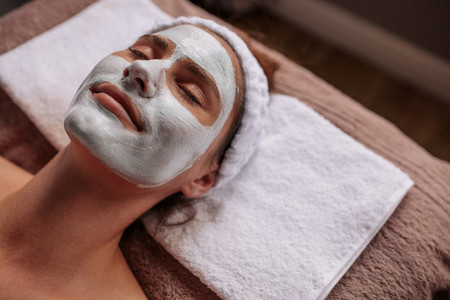 Woman with cosmetic face mask in spa