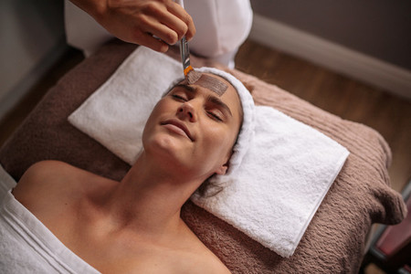 Female getting a facial mask treatment at beauty spa