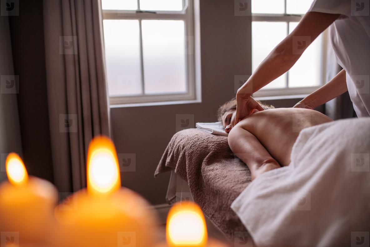 Professional beautician massaging female back