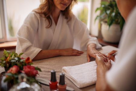 Woman in salon receiving a manicure by beautician