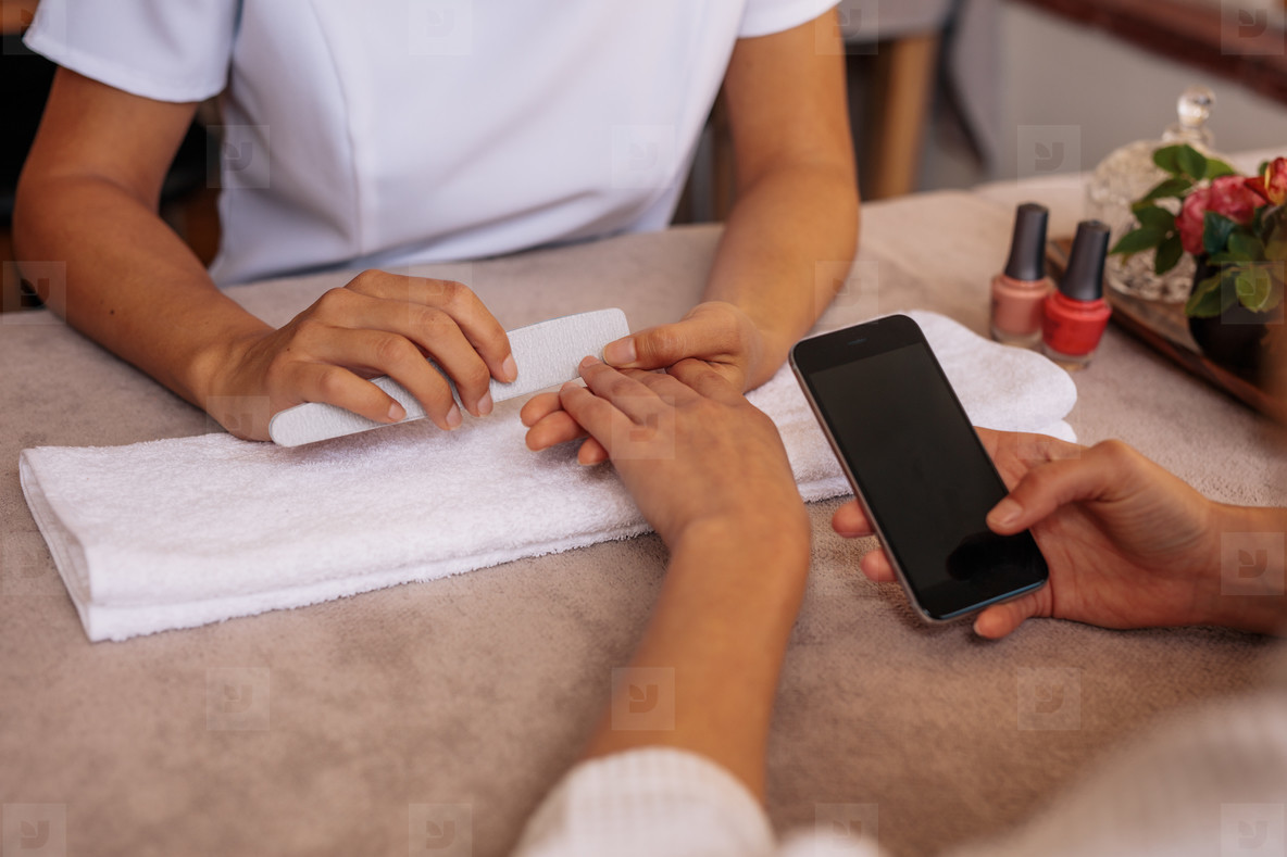Female with smartphone getting manicure at spa