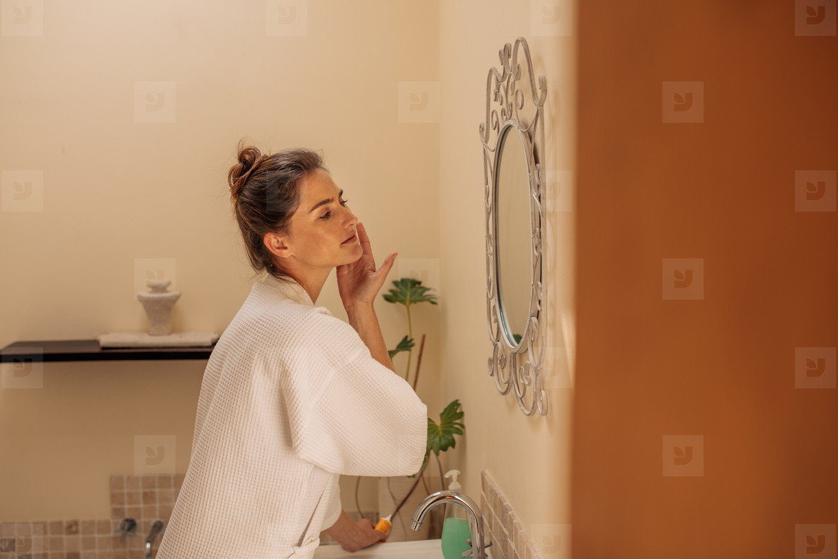 Woman in bathroom putting lotion to her face