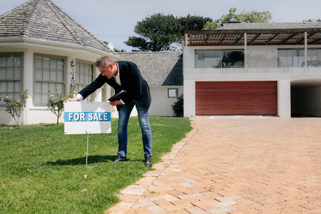 Real estate agent with for sale sign outside a new house
