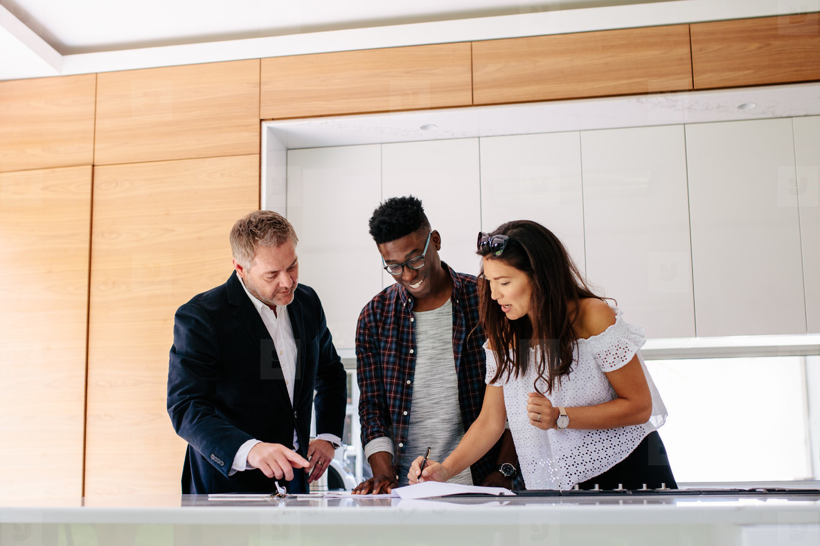 Interracial couple with realtor signing mortgage contract