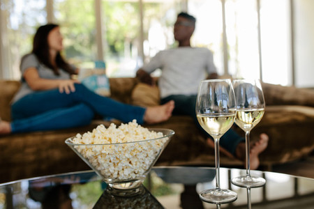 Popcorn and drinks with couple relaxing in background