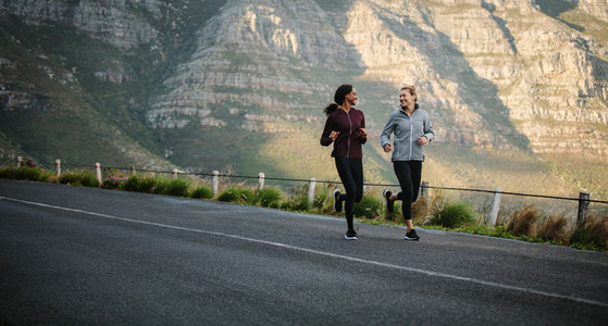 Two women athletes running on road