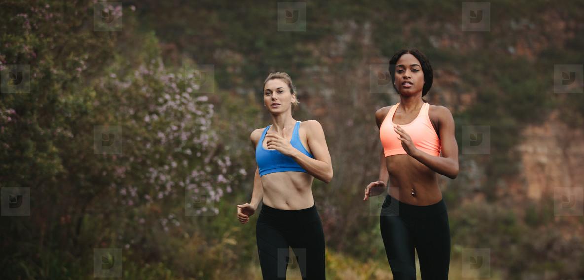 Two women athletes running