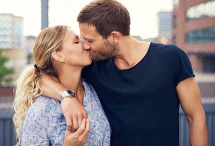 Amorous young couple enjoy a romantic kiss