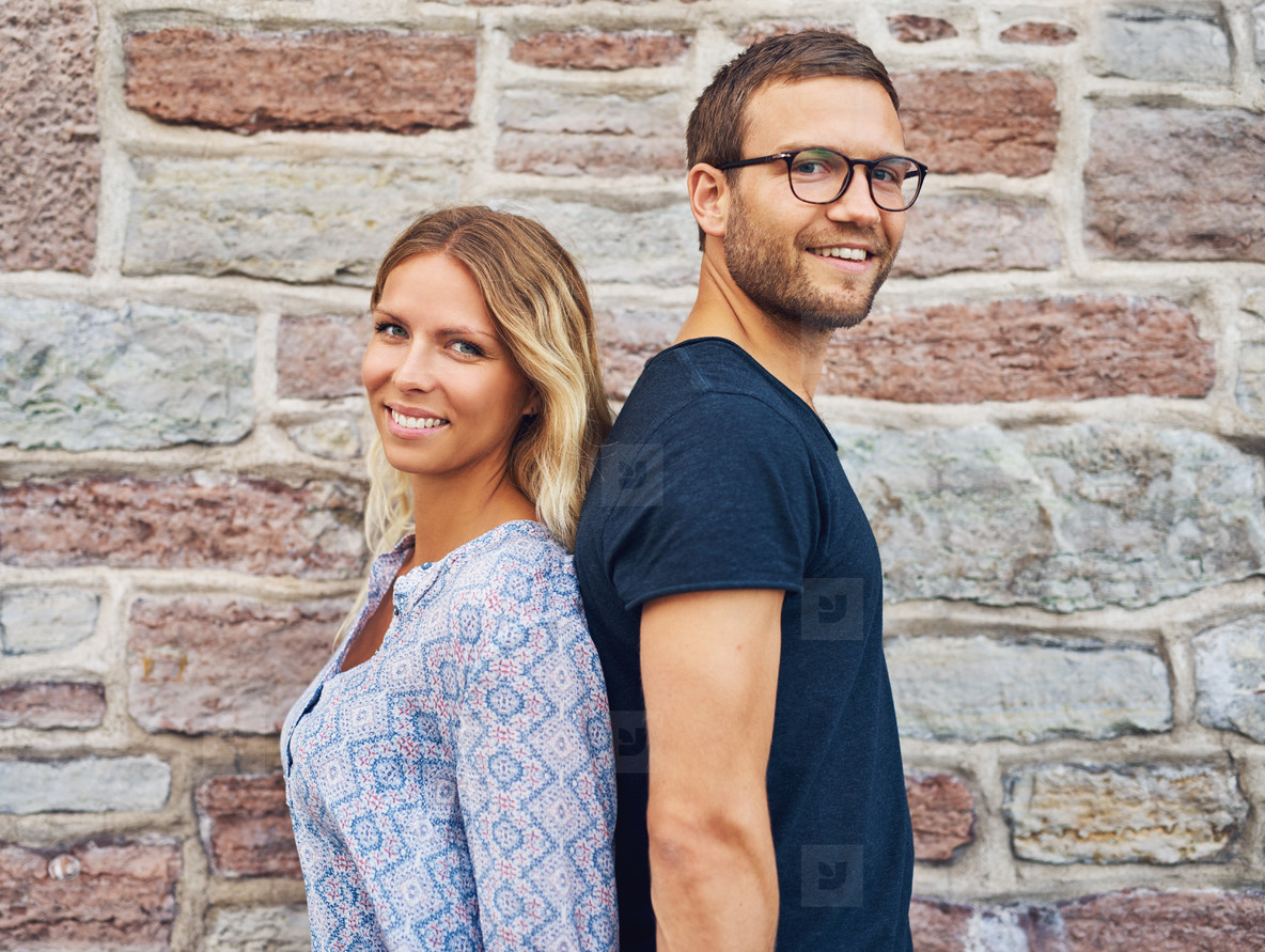 Smiling Couple Standing Back to Back Against Wall