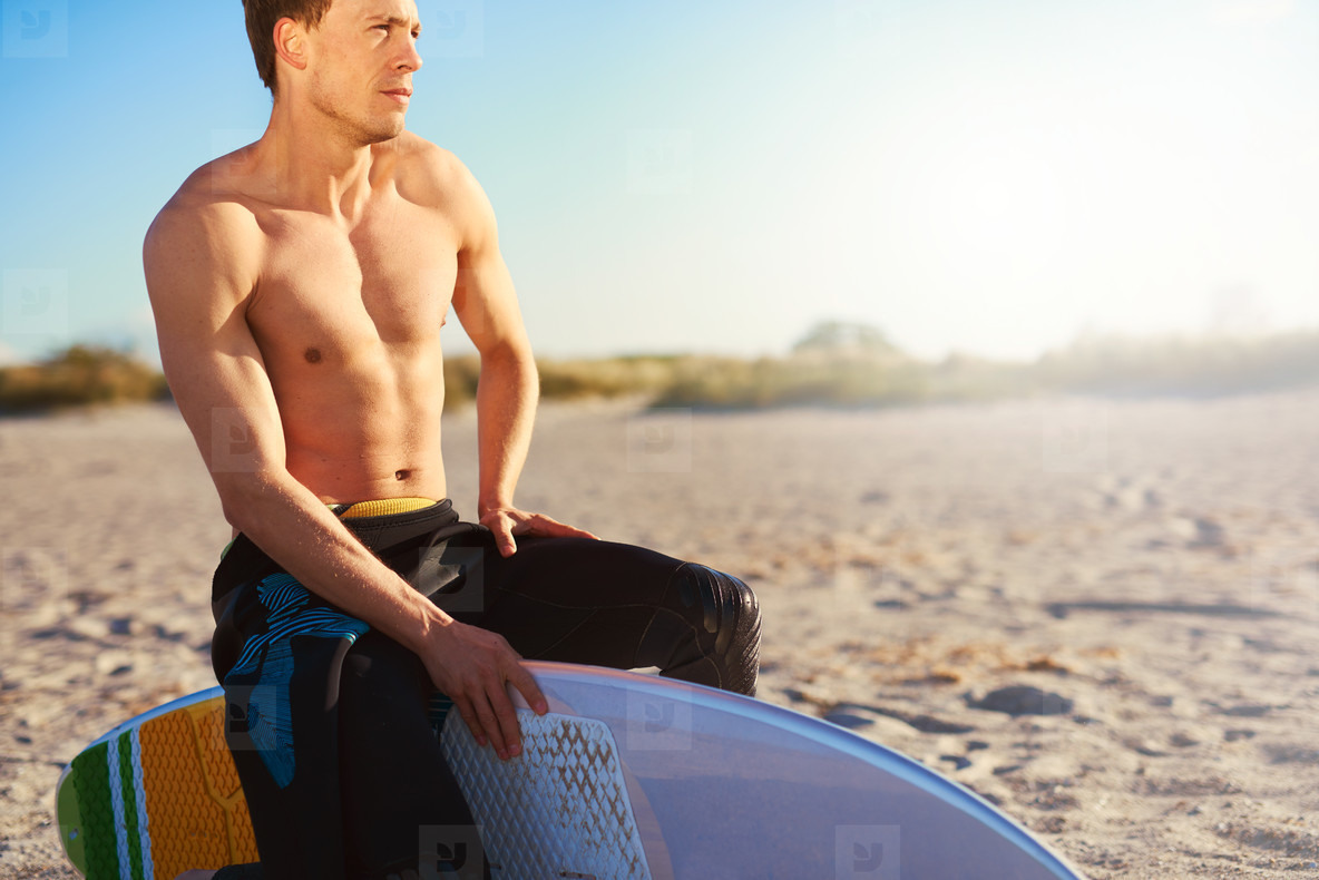 Athletic Man Sitting on Surfboard at Beach Sand