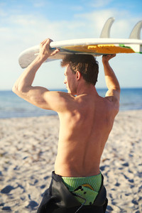 Athletic Guy Holding His Surfboard Over his Head