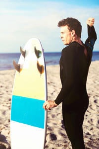 Handsome young surfer zipping up his wetsuit
