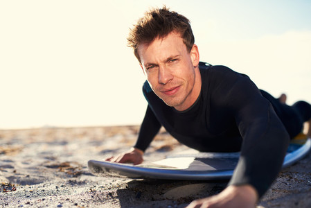 Handsome Surfer in Prone Position on his Surfboard